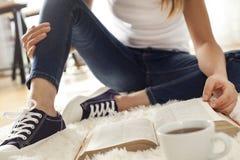 Livre de lecture de jeune femme sur le tapis Photo stock