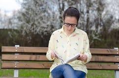 Livre de lecture de jeune fille au parc Photos stock