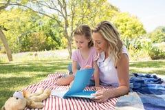 Livre de lecture de mère et de fille en parc Images libres de droits