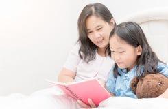 Livre de lecture de mère et de fille sur le lit, Images libres de droits