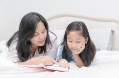 Livre de lecture de mère et de fille sur le lit Photo stock