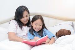 Livre de lecture de mère et de fille sur le lit Photo libre de droits