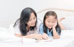 Livre de lecture de mère et de fille sur le lit Images libres de droits