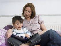 Livre de lecture de mère et de fils sur le lit Photos stock