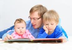 Livre de lecture de père aux enfants photos stock