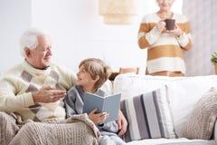 Livre de lecture de petit-fils avec le grand-père Photographie stock libre de droits