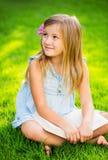 Livre de lecture de petite fille dehors Images stock