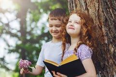 Livre de lecture de petite fille et de garçon en parc Photos stock