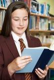 Livre de lecture de port d'uniforme scolaire de fille dans la bibliothèque image libre de droits