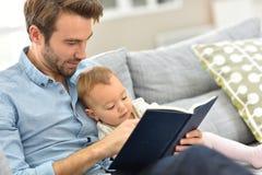 Livre de lecture de père et de bébé à la maison Photo libre de droits