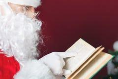 Livre de lecture de Santa Claus avec le conte de fées de Noël Photographie stock