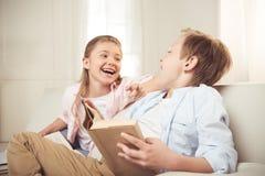 Livre de lecture de soeur et de frère et rire ensemble à la maison Photographie stock