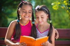 Livre de lecture de soeurs en parc d'été Photo stock