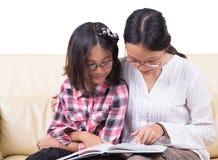 Livre de lecture de soeurs ensemble Photographie stock