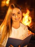 Livre de lecture de sourire de femme à la cheminée détendez photo libre de droits