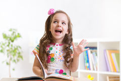 Livre de lecture de sourire de fille d'enfant à la maison Image stock