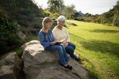Livre de lecture de sourire de petite-fille et de grand-mère dans le jardin Photos libres de droits