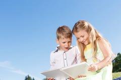 Livre de lecture de sourire mignon de garçon et de fille Photo libre de droits