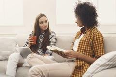 Livre de lecture de deux amis et eBook femelles à la maison Photographie stock