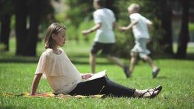 Livre de lecture enceinte de dame en parc, air frais de respiration, repos sain dehors banque de vidéos
