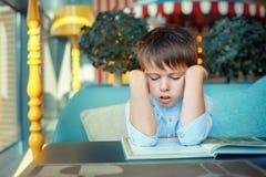 Livre de lecture ennuyeux et fatigué de petit garçon Images libres de droits