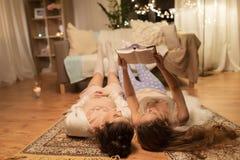 Livre de lecture femelle heureux d'amis à la maison Photos stock
