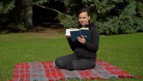 Livre de lecture de femme et thé potable en parc banque de vidéos