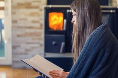 Livre de lecture de femme ? la maison par la chemin?e photos stock