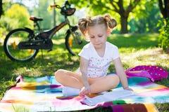 Livre de lecture de fille assez petite en parc vert d'été Photos libres de droits