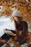 Livre de lecture de fille dehors en hiver photo stock
