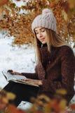 Livre de lecture de fille dehors en hiver photos stock