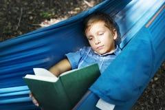 Livre de lecture de garçon dans l'hamac images libres de droits