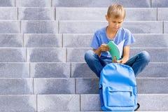 Livre de lecture de garçon se reposant sur les escaliers dehors photo libre de droits