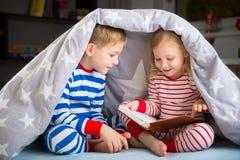 Livre de lecture heureux d'enfants de mêmes parents sous la couverture Images stock