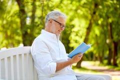 Livre de lecture heureux d'homme supérieur au parc d'été Photos stock