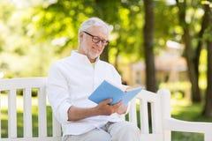 Livre de lecture heureux d'homme supérieur au parc d'été Photo stock