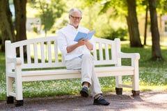 Livre de lecture heureux d'homme supérieur au parc d'été Photographie stock libre de droits