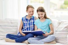 Livre de lecture heureux de deux filles à la maison Photographie stock libre de droits