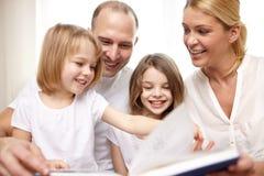 Livre de lecture heureux de famille à la maison Photographie stock