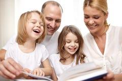 Livre de lecture heureux de famille à la maison Photographie stock libre de droits