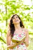 Livre de lecture heureux de femme le ressort photographie stock libre de droits