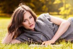 Livre de lecture heureux de femme se couchant sur l'herbe photo stock