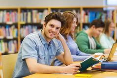 Livre de lecture heureux de garçon d'étudiant dans la bibliothèque Images stock