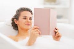 Livre de lecture heureux de jeune femme dans la baignoire Image stock