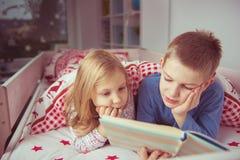 Livre de lecture heureux de deux enfants d'enfant de mêmes parents dans le lit superposé sous le blanke Images libres de droits
