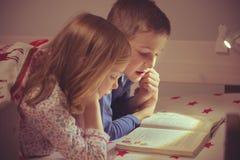 Livre de lecture heureux de deux enfants d'enfant de mêmes parents dans le lit superposé sous le blanke Images stock