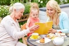 Livre de lecture heureux de famille au café Photo stock