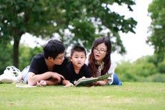 Livre de lecture heureux de famille de latino Photographie stock libre de droits