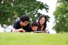 Livre de lecture heureux de famille de latino Images stock