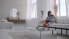 Livre de lecture heureux de fils de mère et d'enfant riant dans le lit Livre heureux de participation de lecture de fils de mère  clips vidéos